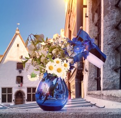 Estonian flag and blue Glass vase and blue white  flowers  medieval house   Tallinn old town estonia europe