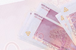10 Estonian kroon bills lies in stack on background of big semi-transparent banknote. Abstract presentation of national currency. Business concept