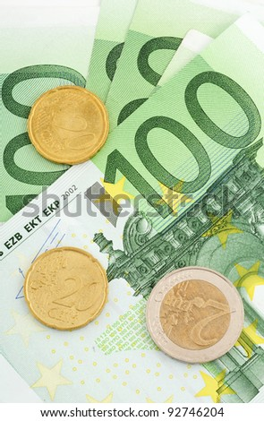 100 Euro bills and some coins in front of a white studio background