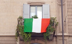 Europe, Italy , Milan - Flag of Italy hanging on the balcony of a house during n-cov19 Coronavirus epidemic emergency