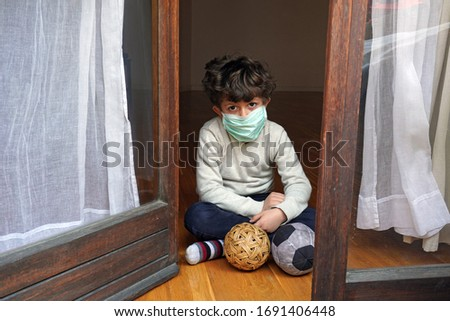 Europe, Italy , Milan - life stile during n-cov19 Coronavirus outbreak epidemic - children boy five years old  with mask during a boring day, sitting near  the window  - quarantine at home        Foto stock ©