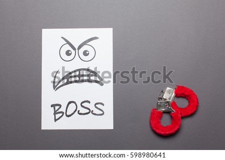 Evil painted boss face with red handcuffs on a white paper  isolated gray background.Sexual harassment concept. Foto stock ©