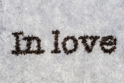 Extreme macro shot of the words IN LOVE typed on white paper. Grungy textured bloody mood.