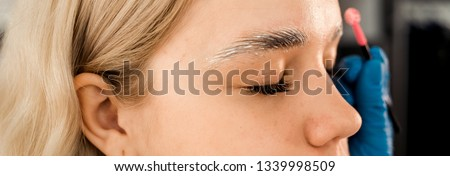 eyebrow styling. eyebrow master draws eyebrows to a girl with blond hair