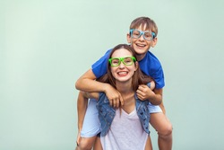 Eyewear concept. The gorgeous freckled brother and sister in casual t shirts wearing trendy glasses over background together. Brother climbed up on the back of a cute sister. Studio shot