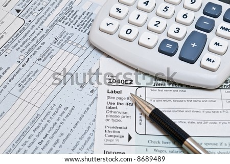 1040EZ income tax forms with pen and calculator