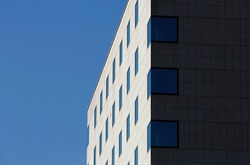 Facade of building with many windows in Sofia, Bulgaria. Blue sky. Perspective view down.