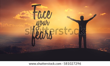 """""""Face your fears"""" text on sunset background. Silhouette of man with raised hands on top of a mountain enjoying the view. #581027296"""