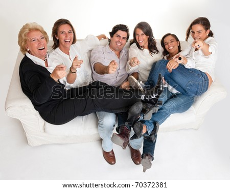 Family group sitting on a sofa laughing and pointing to the camera