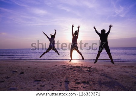 family jumping on the beach on beautiful sunrise, Silhouette shot