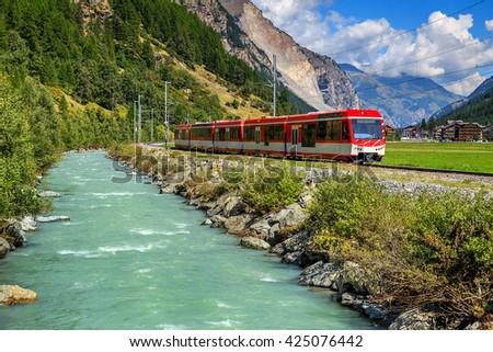 Famous electric red tourist train in Tasch,Valais region,Switzerland,Europe