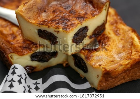 """Photo of  """"far breton"""" a pudding with prunes on a black slate"""