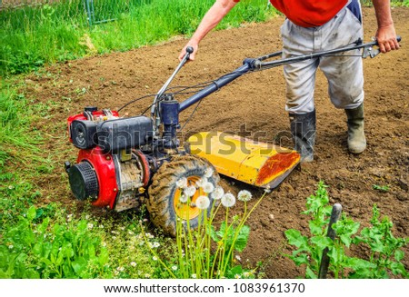 Farmer plows the land with a cultivator. agriculture #1083961370