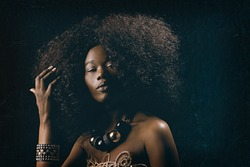 fashion beauty portrait of a beautiful young glamorous African black woman with long curly hair wearing vintage chic 70s style clothes and a necklace