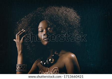 Photo of   fashion beauty portrait of a beautiful young glamorous African black woman with long curly hair wearing vintage chic 70s style clothes and a necklace