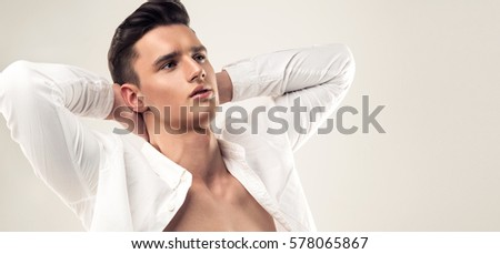 Fashion portrait of a handsome man with trendy hairstyle dressed in a unbuttoned white shirt with dreaming look. Symbol of desire to have perfect vacation and relaxation.    #578065867