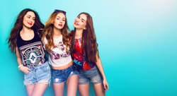 Fashion portrait of   Three best friends posing in studio, wearing summer style outfit and jeans shorts against blue  wall . Girls smiling and having fun.