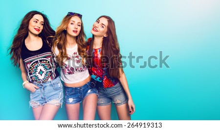Fashion portrait of   Three best friends posing in studio, wearing summer style outfit and jeans shorts against blue  wall . Girls smiling and having fun. #264919313