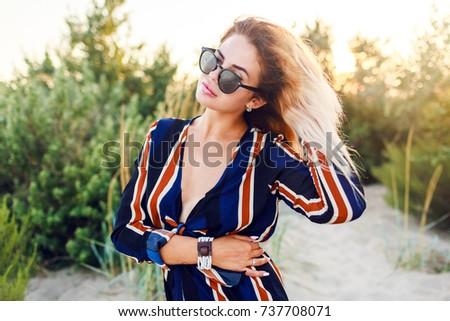 Fashionable  image of amazing blonde model with windy hairs posing  outdoor on sunset. Stylish holiday outfit .Boho accessories.