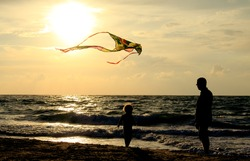 father and daughter flying kite at beach
