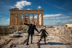 Father and Daughter walk along the Parthenon . Athens, Greece. A tourist family  visiting the hill of the Acropolis.