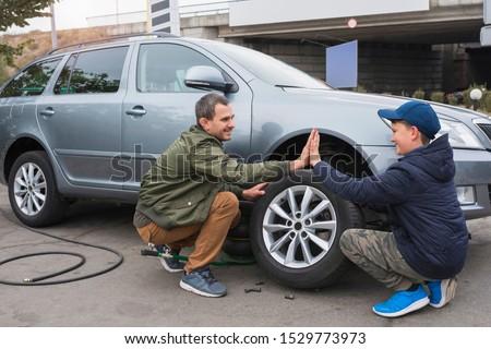 Father and son are repairing a car.  Wheel repair. Auto repair concept.