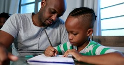 Father mentoring son, dad helping kid with homework study