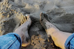Feet buried in sand at the beach. Long legs in ripped blue jeans. Foot with blue nail varnish in wet sand. Young woman photographed from above sitting on the cold sand.