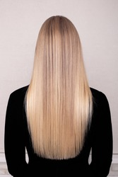 Female back with long blonde healthy hair in hairdressing salon