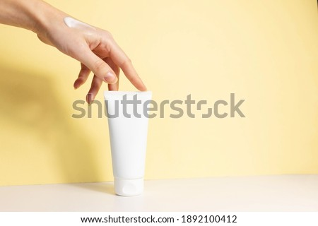 female hand with applied cream touches cosmetic tube on beige background. Concept of cream, hand lotion. Winter skin care. Copy space Foto stock ©