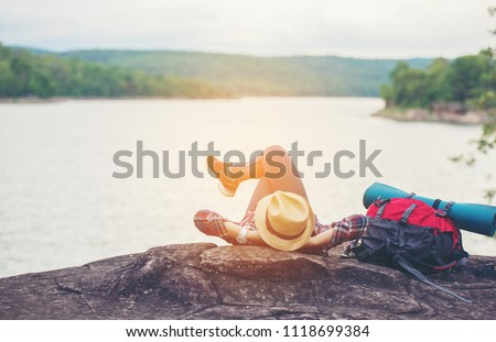 female hiker with backpacks napping on the high peaks at sunrise.