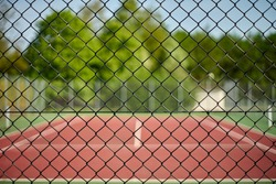 Fenced in tennis court with fence in focus