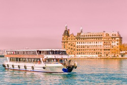Ferry sail down by Bosporus channel on background of Haydarpasa Train Station in Istanbul City, Turkey.