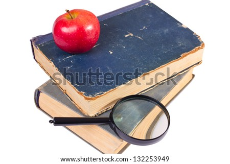 few age-old books, apple and magnifying glass