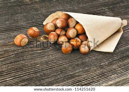 filbert  nut in paper bag on  texture surface  of old wood