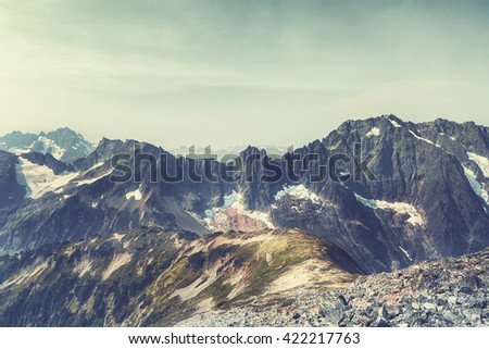 (Film&Instagram Concept): Vintage landscape of Mountains in Northwest America. This vintage landscape has trail, grasses, clouds, mountains, and rocks. This vintage landscape is taken during a day