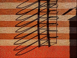 Fire escape on a sunny day. Sunlit red and yellow bricks striped wall with shadows from fire escape. Sunlight and shadows. Abstract geometric composition.