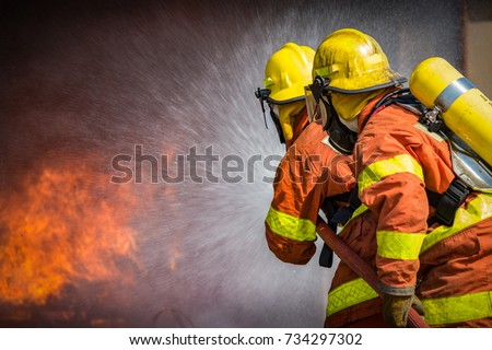 2 firefighters spraying high pressure water to  fire with copy space