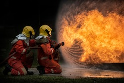 2 firefighters spraying water in fire fighting operation,Fire and rescue training school regularly