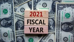 2021 fiscal new year symbol. Wooden blocks with the words '2021 fiscal year'. Beautiful background from dollar bills, copy space. Business and 2021 new fiscal year concept.