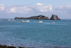 Fishing boats and yachts moored in the bay at high tide in Cancale, famous oysters production town. Brittany, France,