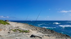 Fishing poles are ready and set on a rocky peninsula on Oahu, Hawaii's north shore