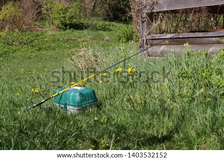 Fishing tackle storage box and spinning rod on green grass. #1403532152