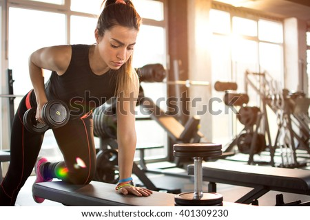 Stock Photo  Fitness girl lifting dumbbell in the morning.