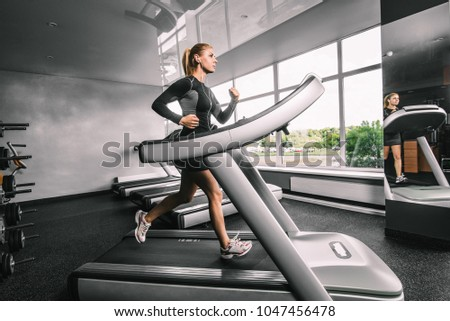 Fitness model trains on a treadmill in the hall