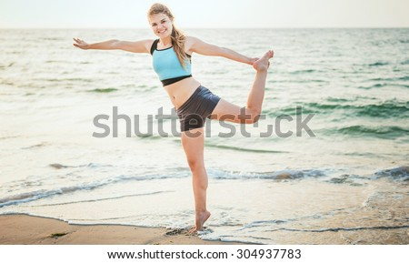 Fitness sport model smiling happy doing exercises during outdoor work out on sunrise. Beautiful caucasian female training outside on seaside in the morning