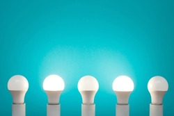 Five energy-saving white LED bulbs in a row on a blue background. The second and fourth lights are on.