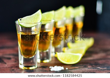 five glasses of alcohol and lime and red chili, a party at the bar, a menu for the bar. Selective focus and copy space, Tequila shots, vodka,whisky, rum #1182584425