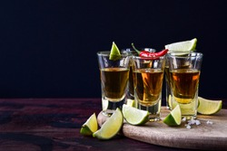 five glasses of alcohol and lime and red chili, a party at the bar, a menu for the bar. Tequila shots, vodka,whisky, rum. Selective focus and copy space