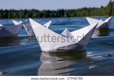 fleet of origami paper boats in lake